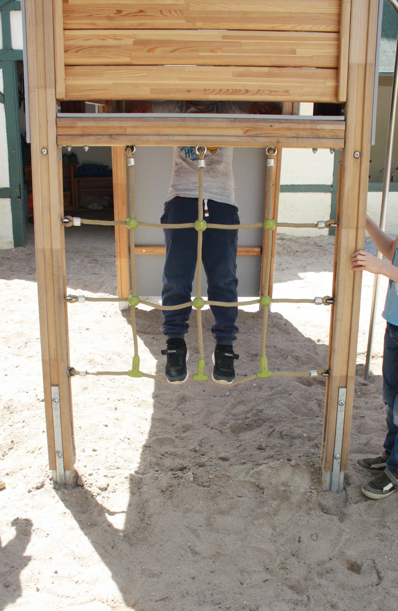 """Marlon (7) ist Fan der Feuerwehrstange. Hier  """"hängt"""" er gerade im Kletternetz ab."""